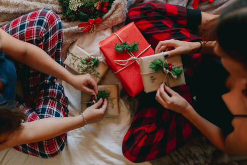 High angle view of two friends opening gifts in cozy bed near christmas tree. Closeup legs of women at home. - ADSF07677