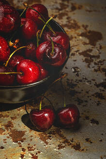 From above tasty appetizing ripe cherry in black brown shining under sunlight on rustic background - ADSF07752