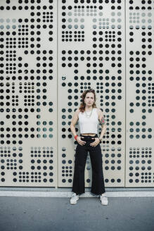 Woman standing against wall with holes in city - MEUF01692