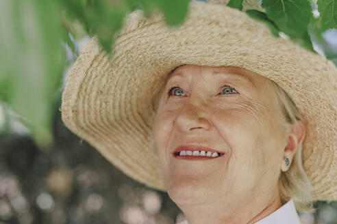 Close-up of smiling senior woman wearing hat looking up - ERRF04117