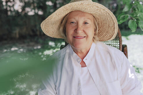 Close-up of smiling senior woman wearing hat sitting on chair in yard - ERRF04123