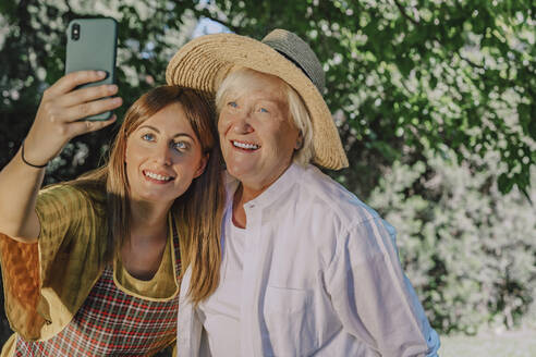 Smiling mid adult woman taking selfie with mother in yard - ERRF04129