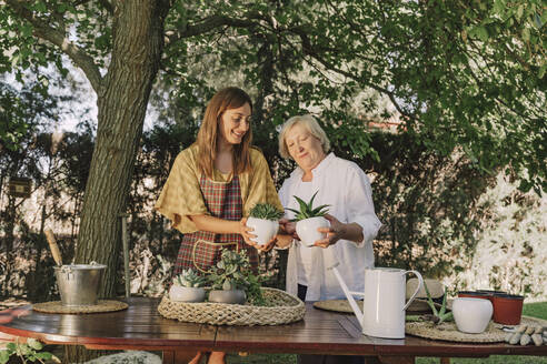 Mother and daughter holding potted plants while standing at table in yard - ERRF04144
