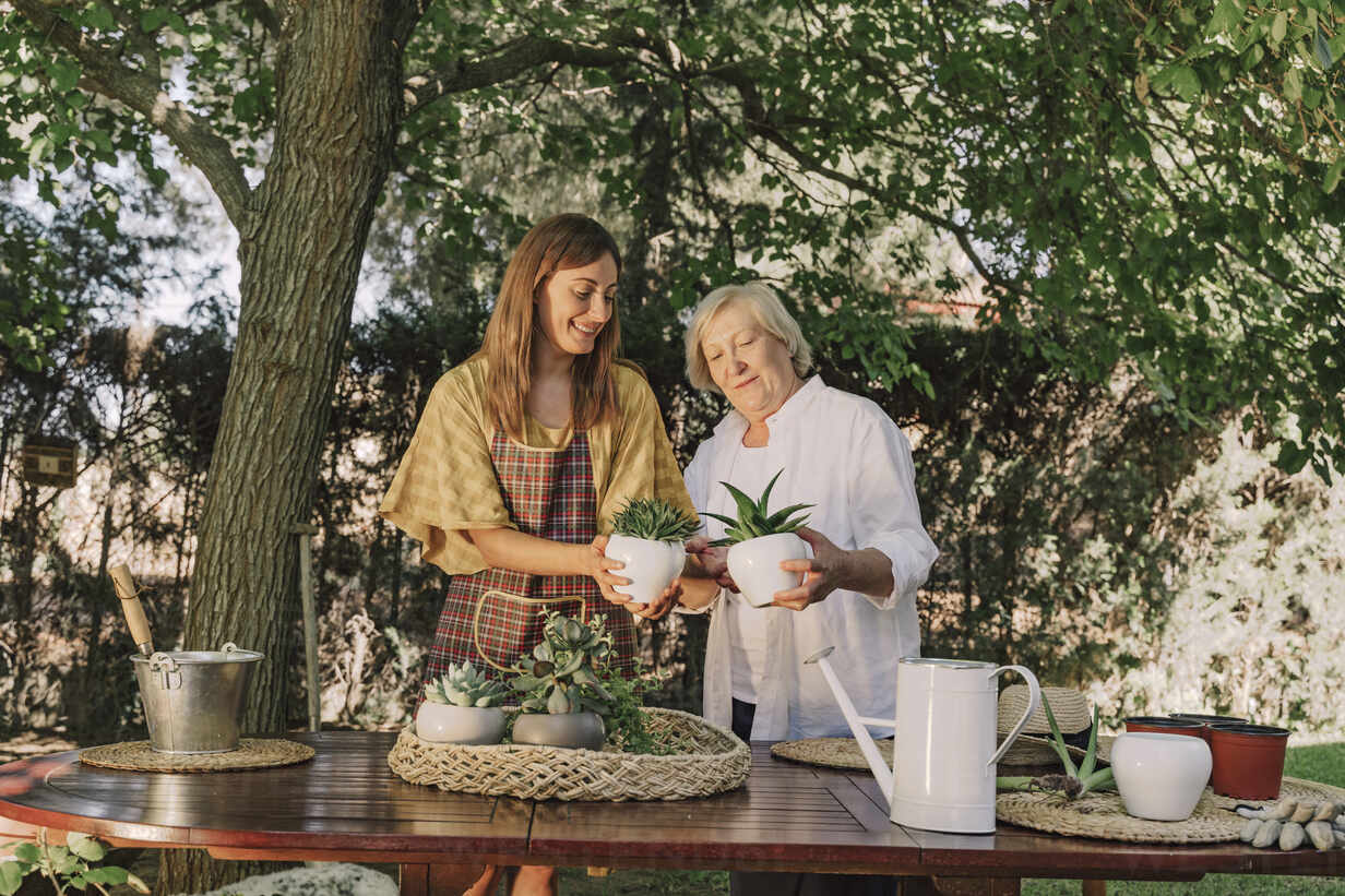 Mother and daughter holding potted plants while standing at table in yard - ERRF04144 - Eloisa Ramos/Westend61