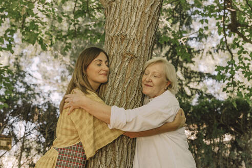 Mother and daughter with eyes closed embracing tree trunk in yard - ERRF04150