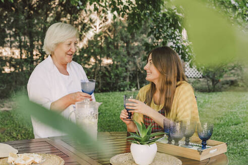 Smiling mother and daughter enjoying drinks while talking in yard - ERRF04159