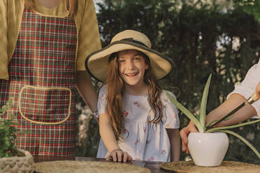 Smiling girl wearing hat standing with mother and grandmother at table in yard - ERRF04168