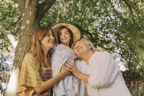 Happy family embracing girl wearing hat against tree in yard - ERRF04174