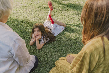 Cute girl with hands on chin talking with family while lying over grassy land in yard - ERRF04180