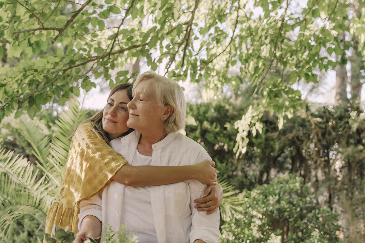 Loving daughter embracing mother while standing against plants in yard - ERRF04186 - Eloisa Ramos/Westend61