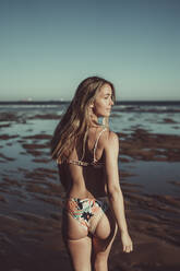 Young woman in bikini looking away while walking at beach against clear sky during sunset - MTBF00592