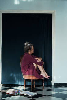 Thoughtful senior woman hugging knees while sitting on chair at home - ERRF04193