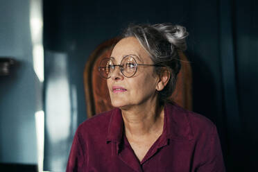 Close-up of thoughtful senior woman wearing eyeglasses looking away sitting at home - ERRF04202