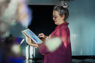 Senior woman wearing eyeglasses drawing in book while standing at home - ERRF04205