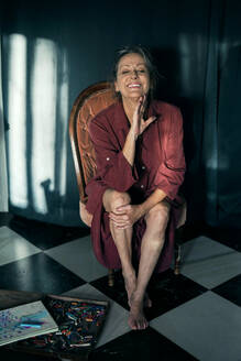 Smiling senior woman with eyes closed sitting on chair at home - ERRF04208