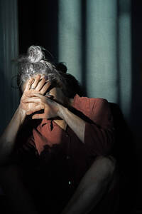 Senior woman shielding eyes while sitting against wall at home - ERRF04217