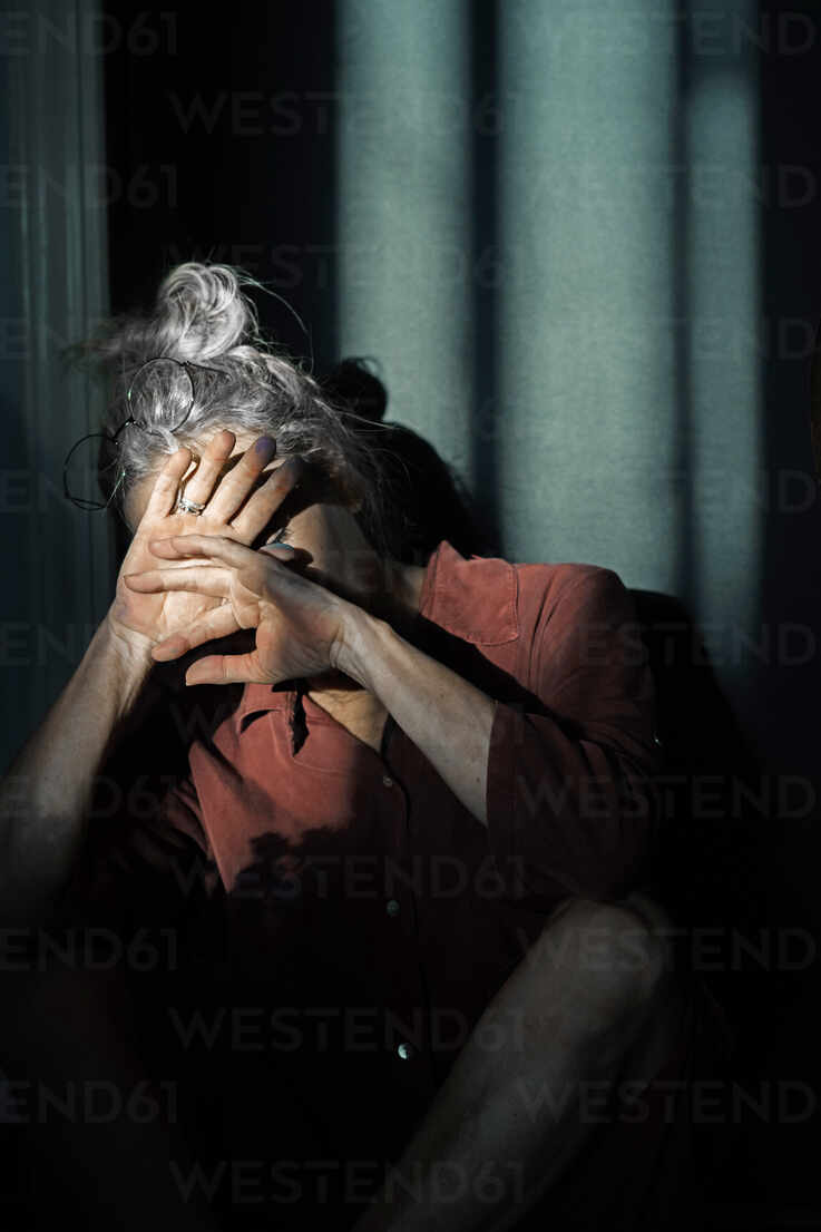 Senior woman shielding eyes while sitting against wall at home - ERRF04217 - Eloisa Ramos/Westend61