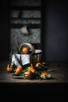 Mandarins and basket on table - ADSF08664