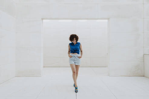 Stylish woman with curly hair walking on tiled floor against wall - GMLF00378