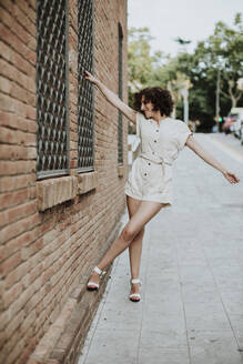 Mid adult woman with arms outstretched standing on street by brick wall in city - GMLF00387