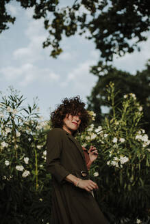 Mid adult woman with curly hair wearing coat standing against plants in park - GMLF00396