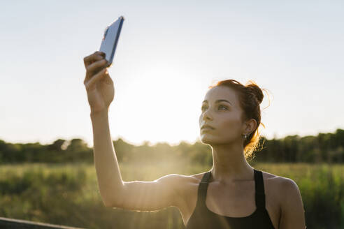 Young woman using phone against clear sky - EGAF00614