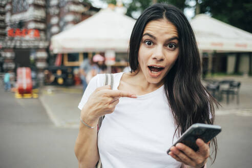 Surprised young woman pointing towards smart phone while standing in amusement park - OYF00180