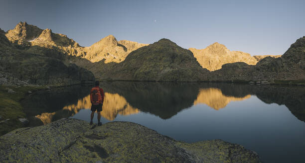 A young man with backpack looking at lake reflection, Sierra de Gredos - CAVF87808