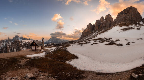 Mountain landscape with rural house located in snowy valley surrounded by danger rocks under open cloudy sky in Dolomites Italy - ADSF08835