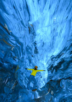 Woman with arms outstretched in ice cave, Iceland - TOVF00229