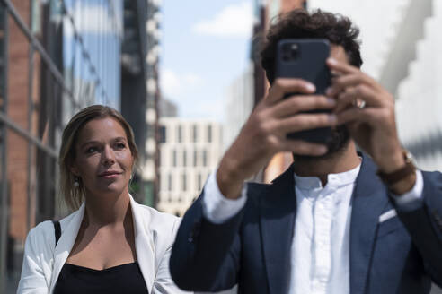 Businessman with smartphone and businesswoman in business district in the city - HPSF00046
