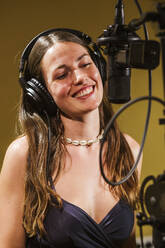 Singer with headphones at microphone in recording studio - LJF01738