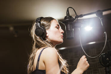 Singer with headphones at microphone in recording studio - LJF01744