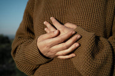 Hands of a woman wearing brown pullover - RCPF00279