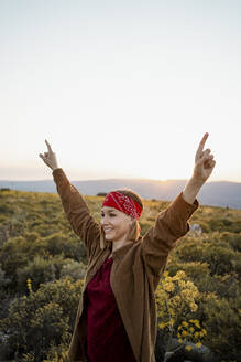 Happy woman with raised arms in the countryside - RCPF00282