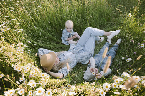 Mother with daughter and son lying on flower field - EYAF01236
