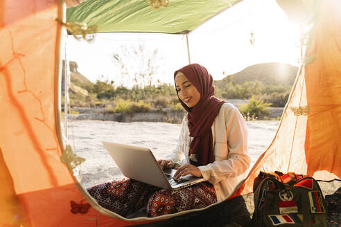 Young woman wearing Hijab using laptop at a tent - MPPF00972