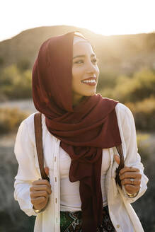 Smiling young tourist woman wearing Hijab in desert landscape looking around - MPPF00975