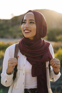 Smiling young tourist woman wearing Hijab in desert landscape looking around - MPPF00978