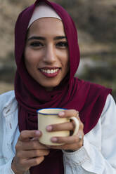 Portrait of smiling young woman wearing Hijab holding a mug - MPPF00996
