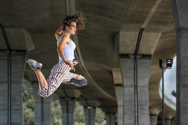 Young womann doing acrobatics and jumping under bridge - STSF02580