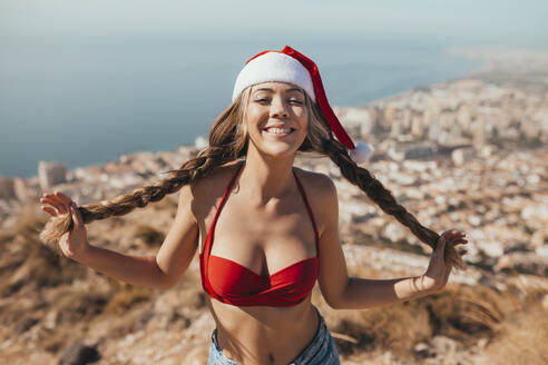 Portrait of happy young woman with santa hat above the coastal city of Almeria, Spain - MIMFF00139