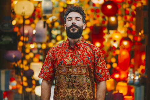 Attractive bearded man with colorful shirt standing in front of lamps with eyes closed - MIMFF00150