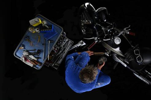 Top view of man repairing vintage motorcycle with black background (Ardie RZ) - SRSF00657