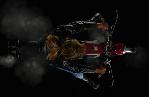Top view of woman on vintage motorcycle with black background and smoke (Zuendapp KS 125 Sport) - SRSF00663
