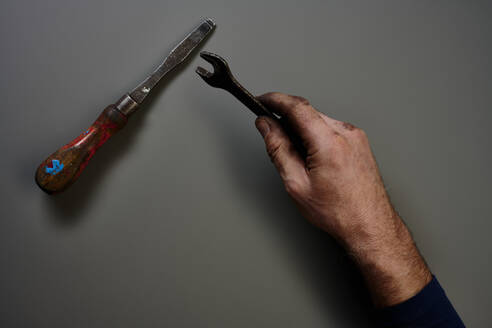 Top view of hand with tools in front of grey background - SRSF00666