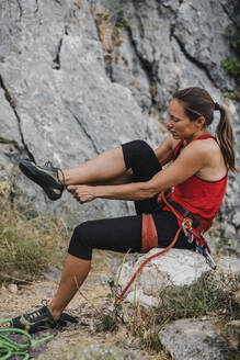 Female climber wearing shoe while sitting on rock - DMGF00115