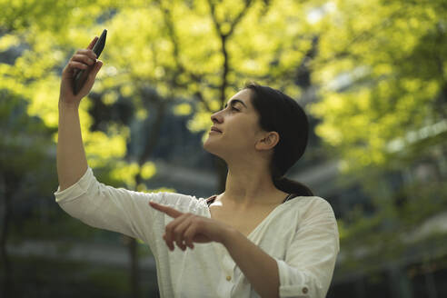 Young woman taking selfie through smartphone against trees - HPSF00055