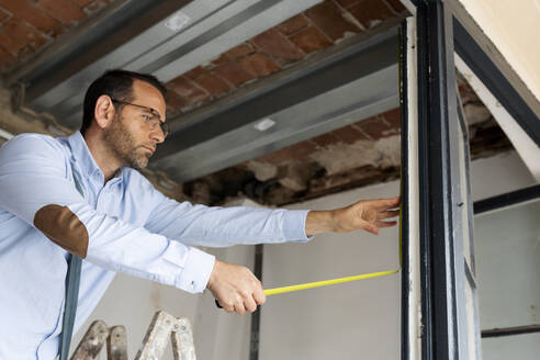 Architect using tape measure on window frame in a house under construction - VABF03301