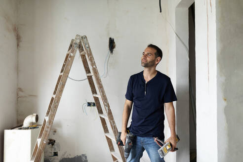 Confident construction worker standing in a house under construction - VABF03322